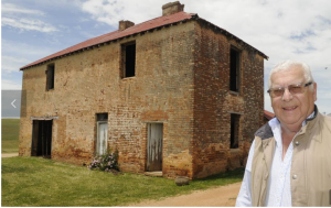 CONVICT HISTORY: Paul Hennessy with the 200-year-old two-storey convict barracks on Macquarie, the former home of Blue Mountains explorer William Lawson. Photo: CHRIS SEABROOK